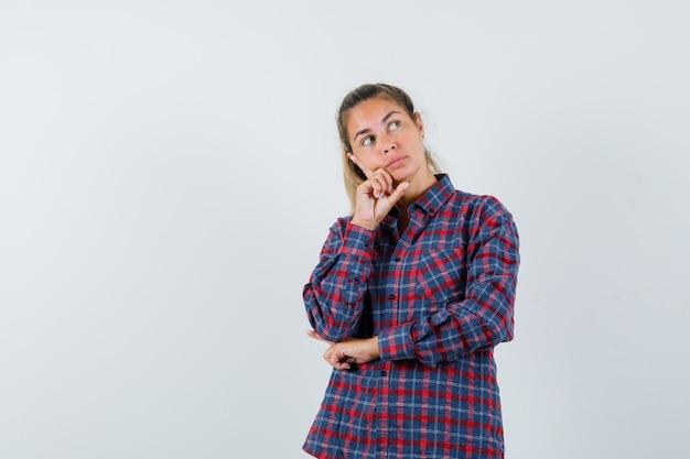 Молодая женщина, стоящая в позе мышления в клетчатой рубашке и задумчиво выглядящая