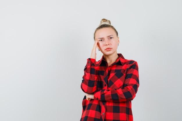チェックシャツでポーズを考えて立って悲しそうな若い女性