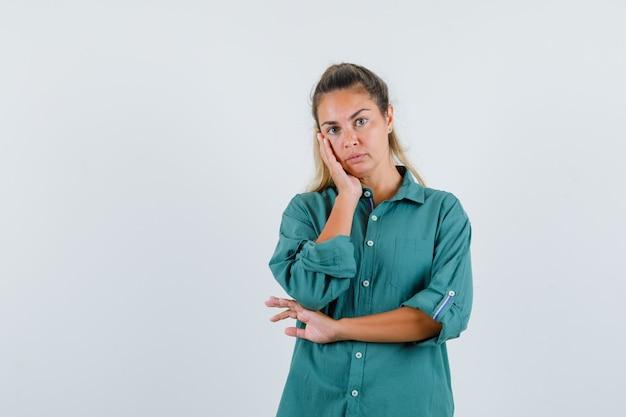 녹색 블라우스에 생각 포즈에 서 있고 잠겨있는 찾고 젊은 여자