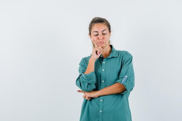 Молодая женщина, стоящая в позе мышления в зеленой блузке и задумчиво выглядящая