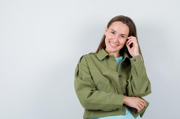 緑のジャケットを着て、陽気に見えるポーズを考えて立っている若い女性。正面図。