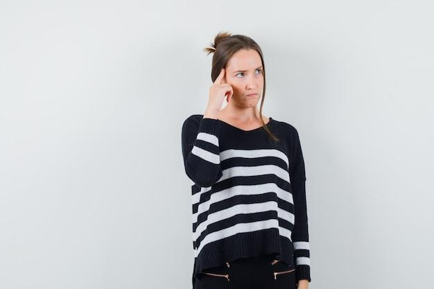 Молодая женщина, стоящая в задумчивой позе в полосатом трикотажном белье и черных брюках, задумчивая