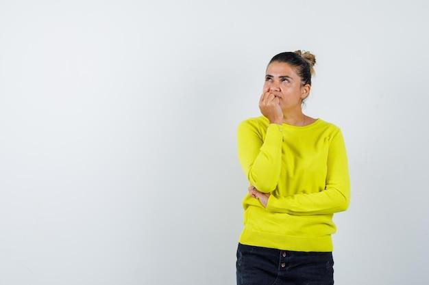 Молодая женщина, стоящая в позе размышления в желтом свитере и черных штанах, задумчивая