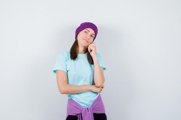 생각하는 포즈로 서 있는 젊은 여성, 파란색 티셔츠, 보라색 비니를 입은 손에 뺨을 기대고 수심에 찬 앞모습.