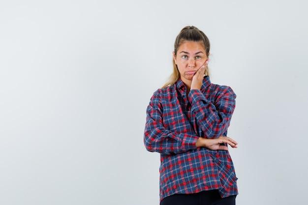 Молодая женщина, стоящая в позе размышления, прислоненная щекой к ладони в клетчатой рубашке и задумчивая