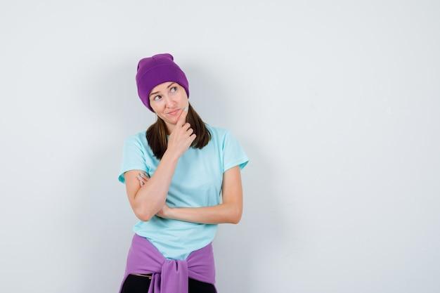 思考ポーズで立っている若い女性、青いtシャツ、紫色のビーニーで手に寄りかかって、物思いにふける。正面図。