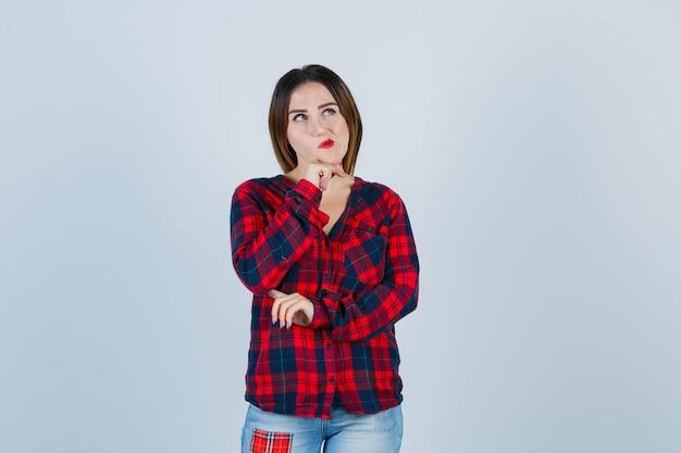思考ポーズで立っている若い女性、チェックのシャツ、ジーンズで手に顎を支え、物思いにふける。正面図。