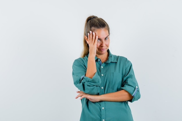 Молодая женщина, стоящая в позе мышления, кладет руку на лицо в зеленой блузке и выглядит задумчиво