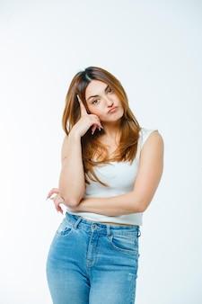 Молодая женщина, стоящая в позе мышления