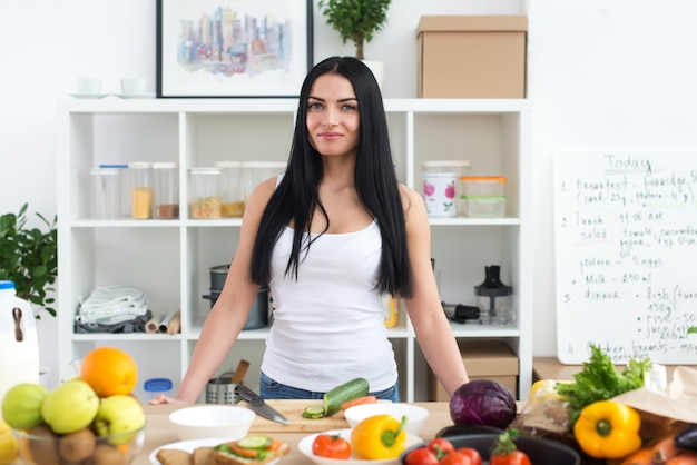Young woman standing in the kitchen surrounded by mixed fresh vegetables