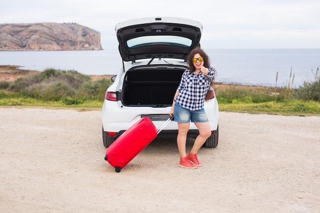 웃 고 갈 준비 차 뒤쪽 근처에 서있는 젊은 여자. 여름 여행