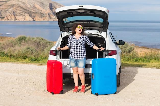 車の後ろの近くに立って笑顔で行く準備をしている若い女性。夏のロードトリップ