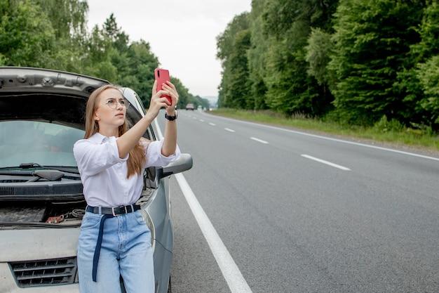 壊れた車の近くに立って自分撮りをしている若い女性