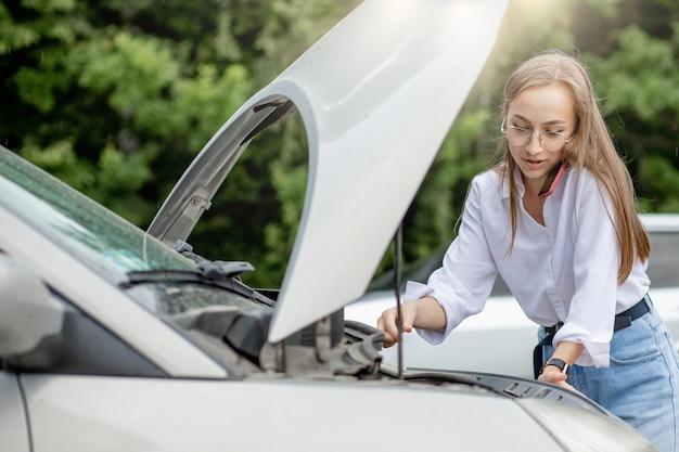 젊은 여자가 그녀의 차량에 문제가있는 후드를 팝업으로 세분화 된 자동차 근처에 서. 견인 트럭 또는 기술 지원을 기다리고 있습니다. 한 여성이 서비스 센터에 전화를 겁니다.