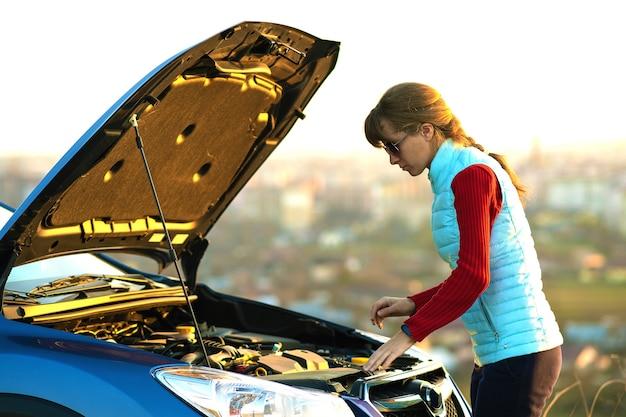 그녀의 차량에 문제가 팝업 후드와 함께 세분화 차 근처에 서있는 젊은 여자