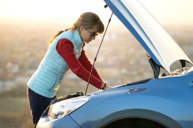 壊れた車の近くに立っている若い女性は、彼女の車に問題を抱えているポップアップフード。