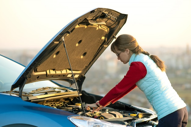 Young woman standing near broken down car with popped up hood having trouble with her vehicle.