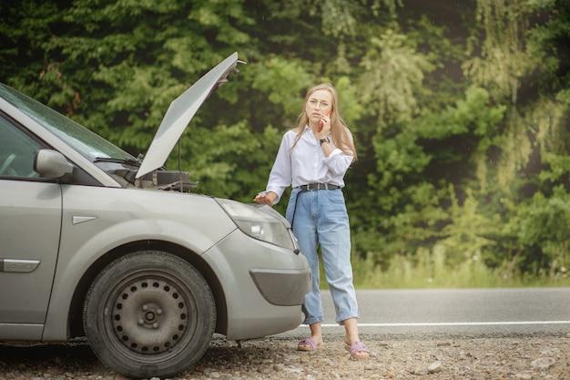 Молодая женщина, стоящая возле разбитой машины с поднятым капотом, испытывает проблемы с ее автомобилем.