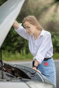 壊れた車の近くに立っている若い女性が彼女の車に問題を抱えているポップアップフード