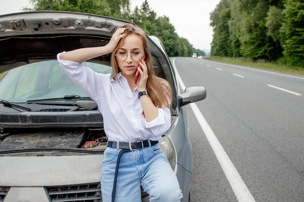 ポップアップフードで壊れた車の近くに立っている若い女性