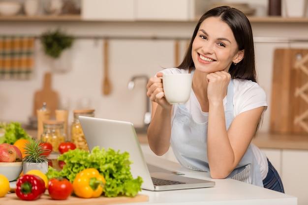 Молодая женщина, стоящая возле стола на кухне, улыбаясь, с чашкой чая