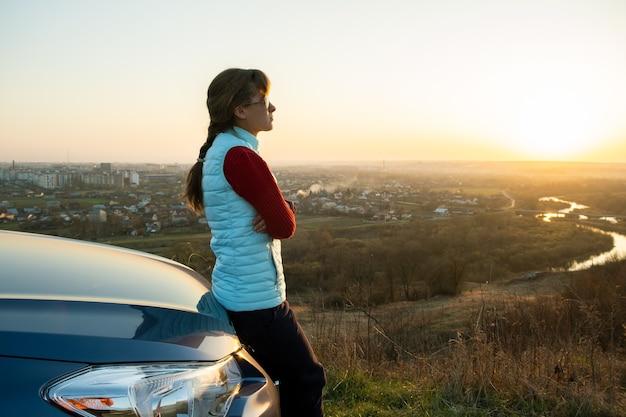 暖かい夕日の景色を楽しんでいる彼女の車の近くに立っている若い女性。夜の地平線を見ている車のボンネットに寄りかかって女の子の旅行者。