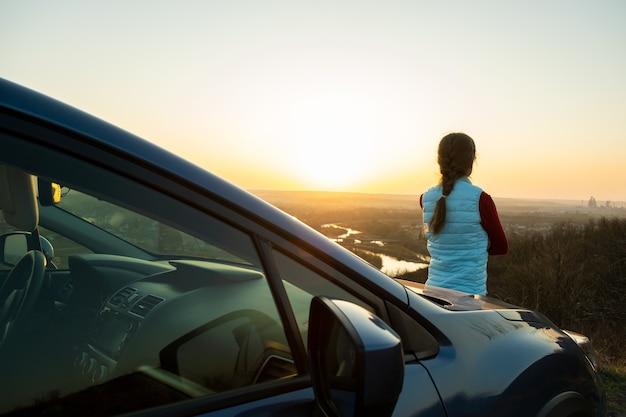 暖かい夕日の景色を楽しんでいる彼女の車の近くに立っている若い女性。