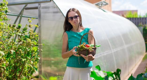 야외에서 그녀의 온실 근처에 서있는 젊은 여자