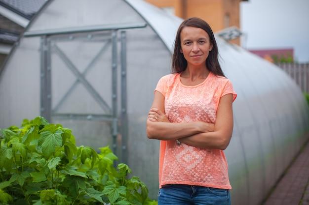 그녀의 온실 근처에 서있는 젊은 여자