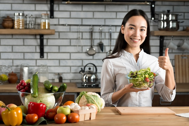 Young woman standing near kitchen counter showing thumb up sign holding vegetables salad