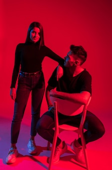 Young woman standing near man on chair