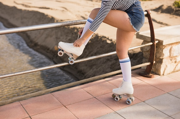Young woman standing near the railing tying lace on roller skate