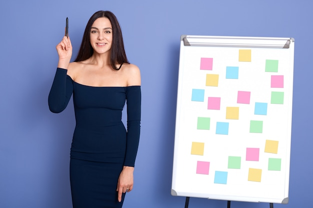 フリップチャートの付箋の近くに立って、手を上げてペンを持って、素晴らしいビジネスアイデアを持って、青い背景に分離されたドレスでポーズをとる若い女性。