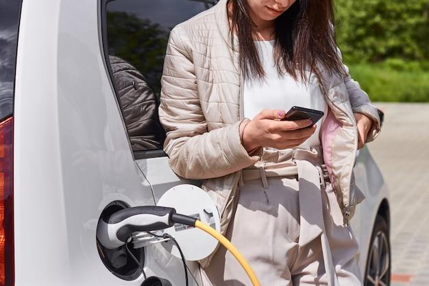 Молодая женщина стоит возле электромобиля с мобильным телефоном в руке и ждет зарядки автомобильного аккумулятора.