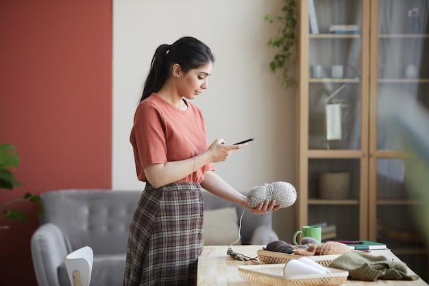 羊毛のボールを持ってテーブルの近くに立って、彼女の携帯電話で写真を作る若い女性