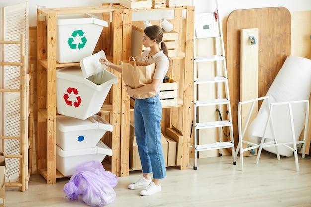木製の棚の近くに立って、ゴミをコンテナに分類する若い女性