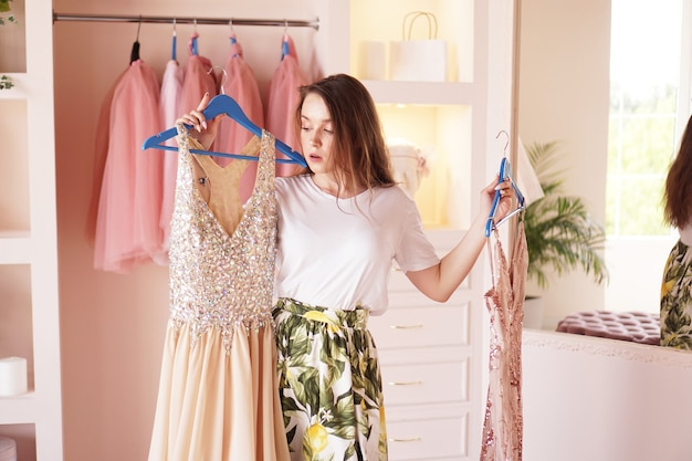 Young woman standing near wardrobe, holding dress on hangers, trying to decide what to wear