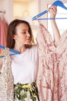 ワードローブの近くに立って、ハンガーにドレスを持って、何を着るかを決めようとしている若い女性。楽屋で服を選ぶきれいな女性。