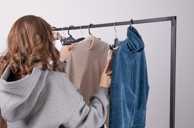 옷의 전체 옷장 선반 근처에 서서 옷을 선택하는 젊은 여자. 쇼핑 및 소비 또는 스타일리스트 개념. 여자 옷가게에서 계절 업데이트를 선택합니다.