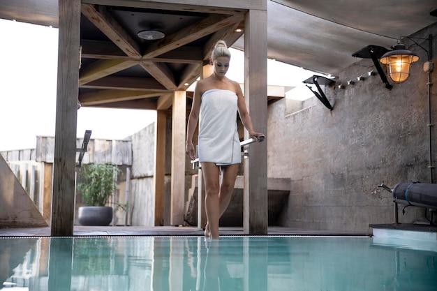 수영장 옆에 서 있는 젊은 여자