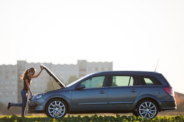 터진 된 후드 아래를보고 차 옆에 서있는 젊은 여자
