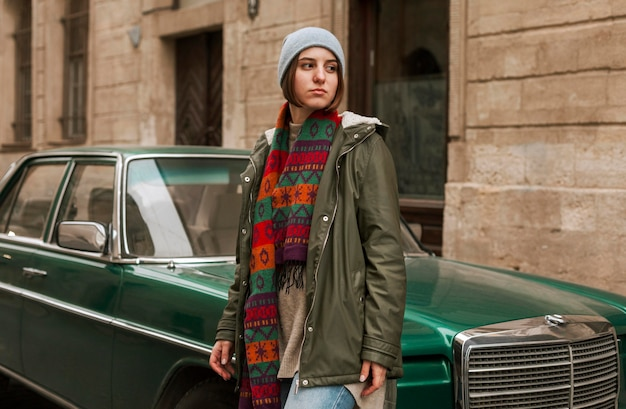 緑の車の横に立っている若い女性