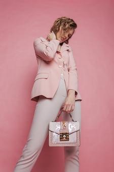 ピンクの上に立って、ピンクのバッグを保持している若い女性。