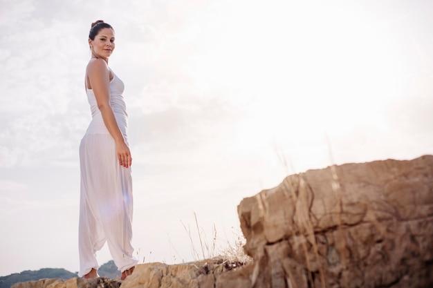 Молодая женщина, стоя на скале