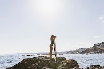 Young woman standing on rocky sea shore with surfboard