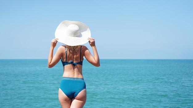 海の近くの砂の上に立ち、白い帽子をかぶった若い女性