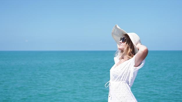바다 근처 모래에 서서 흰 모자를 들고 젊은 여자