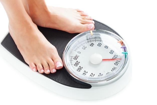 Молодая женщина, стоящая на весах