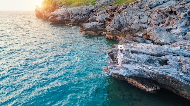 岩の上に立って、sichang島の海岸と夕日を見ている若い女性。
