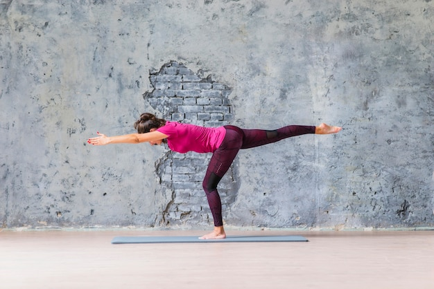 Young woman standing on one leg doing fitness exercise against grey wall